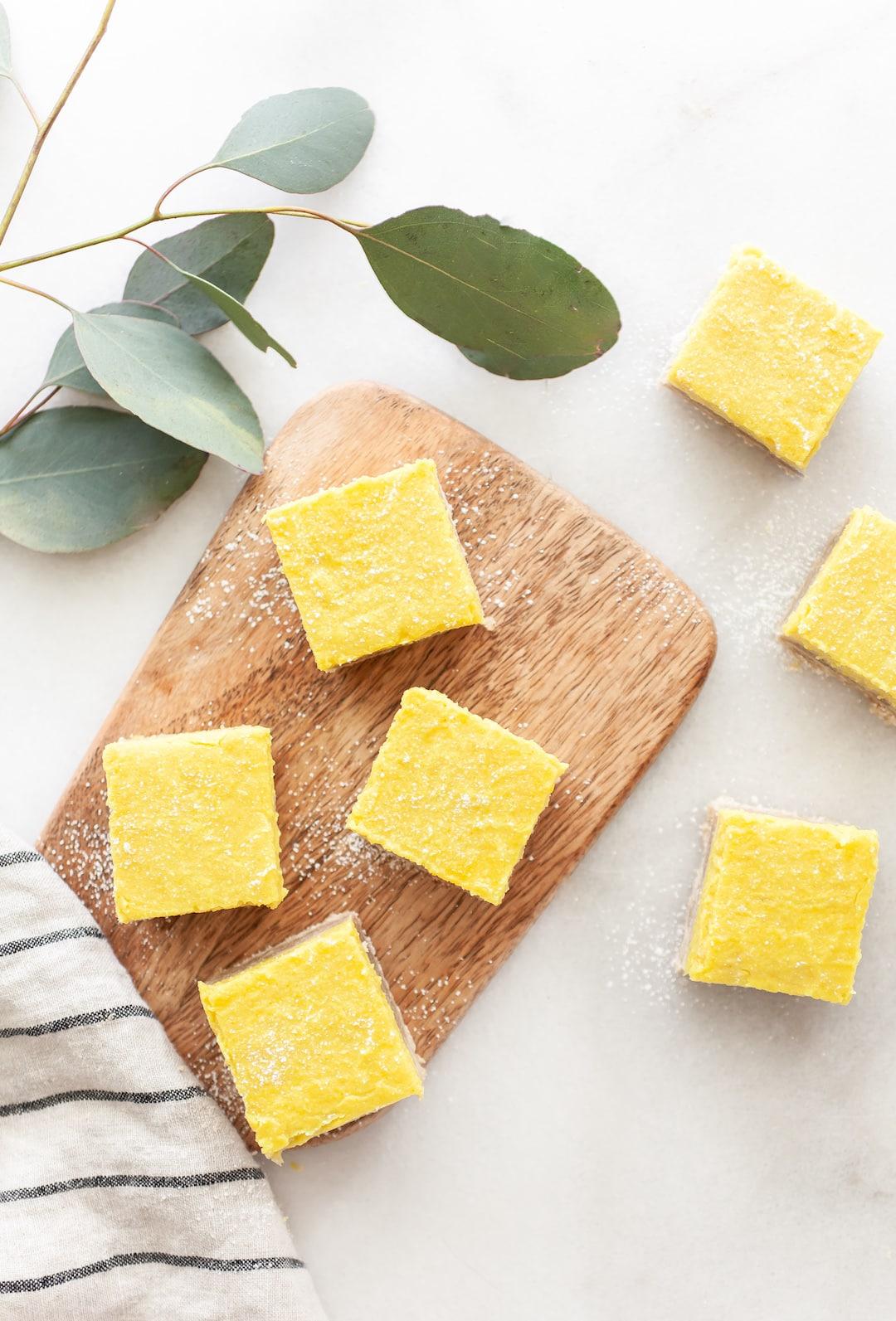 Overhead view of Best Vegan Lemon Bars on a wood platter on marble background