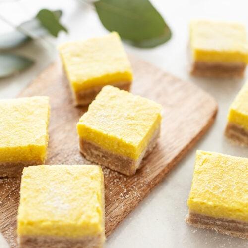 Side view of Best Vegan Lemon Bars on a wood platter