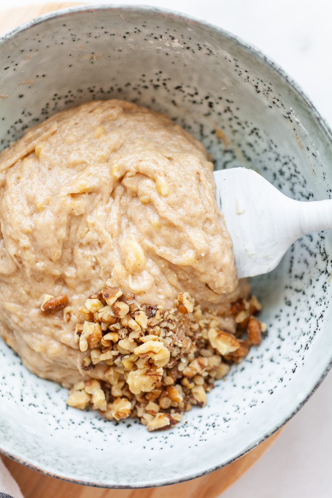 Instant Pot Banana Bread batter in a bowl with walnuts and a white spatula