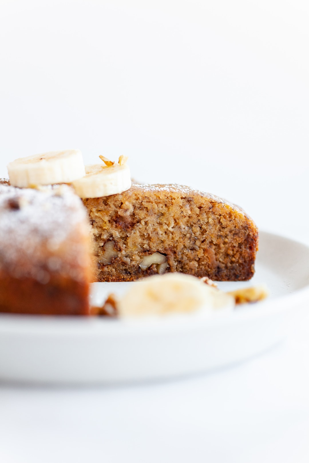 Side view of a loaf of instant pot banana bread with a slice cut out of it