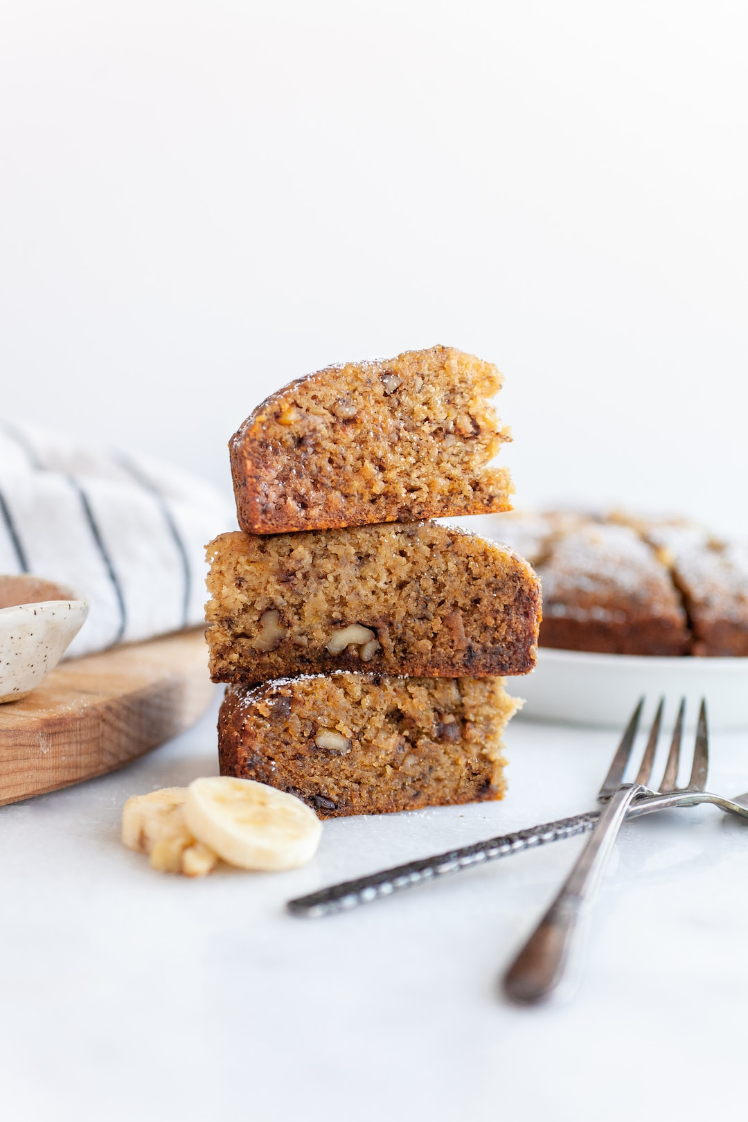 Three pieces of Close up of instant pot banana bread topped with powdered sugar and banana slices stacked