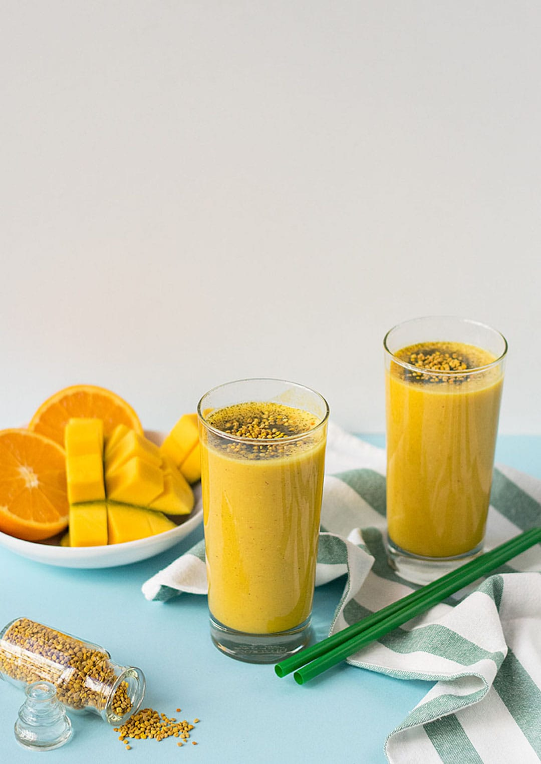 two glasses of bee pollen smoothie on a green table top