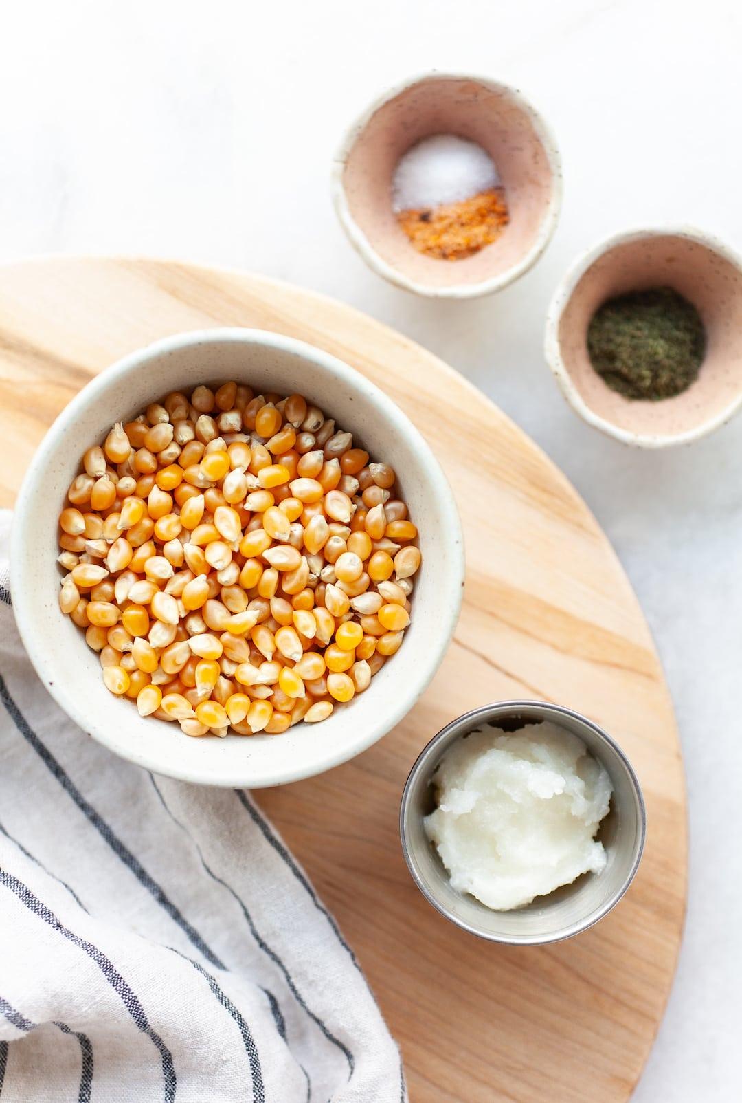 instant pot popcorn ingredients on a wooden board - popcorn kernels, coconut oil, seasonings