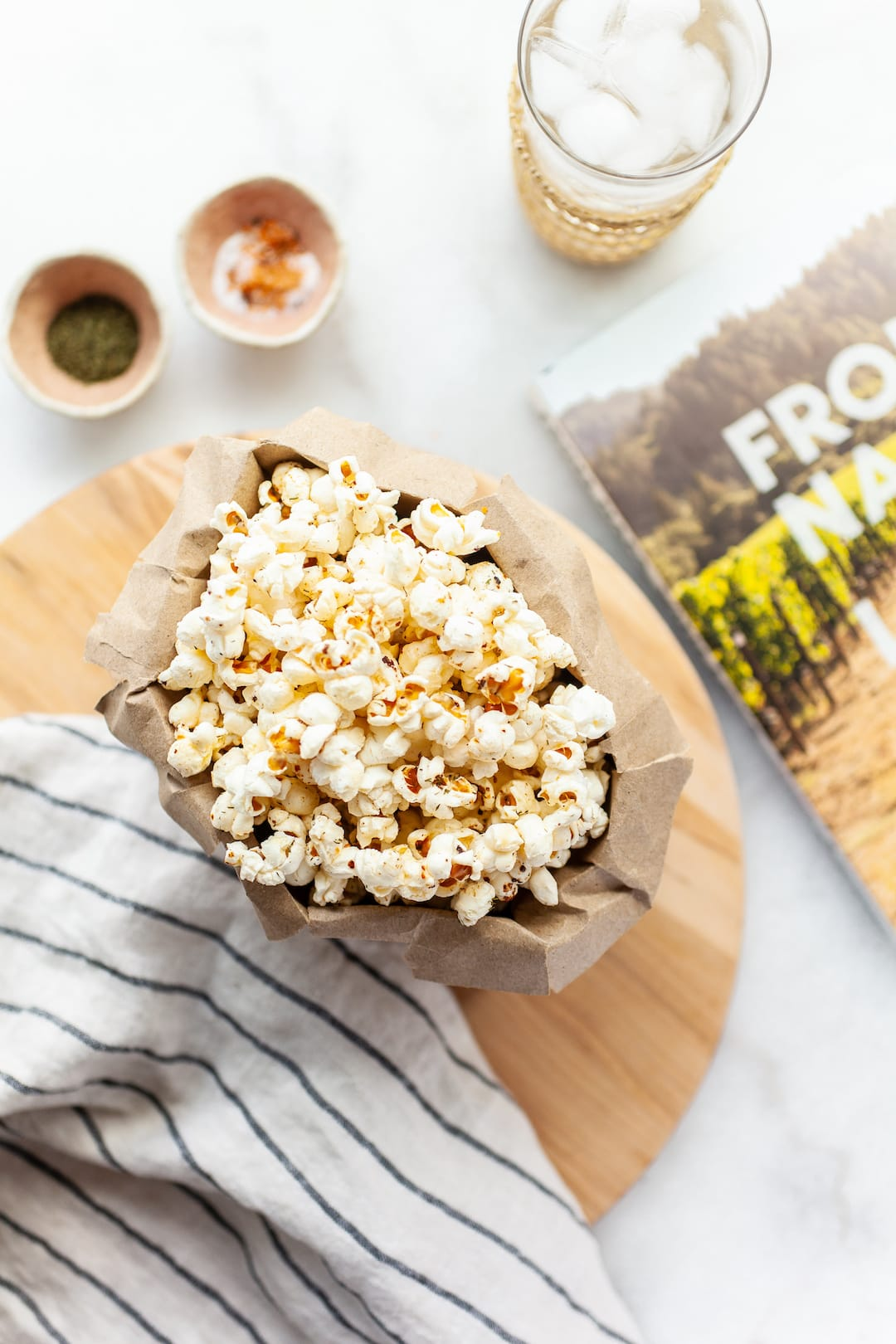 instant pot popcorn in a paper bag on a wooden board with a book beside it for styling
