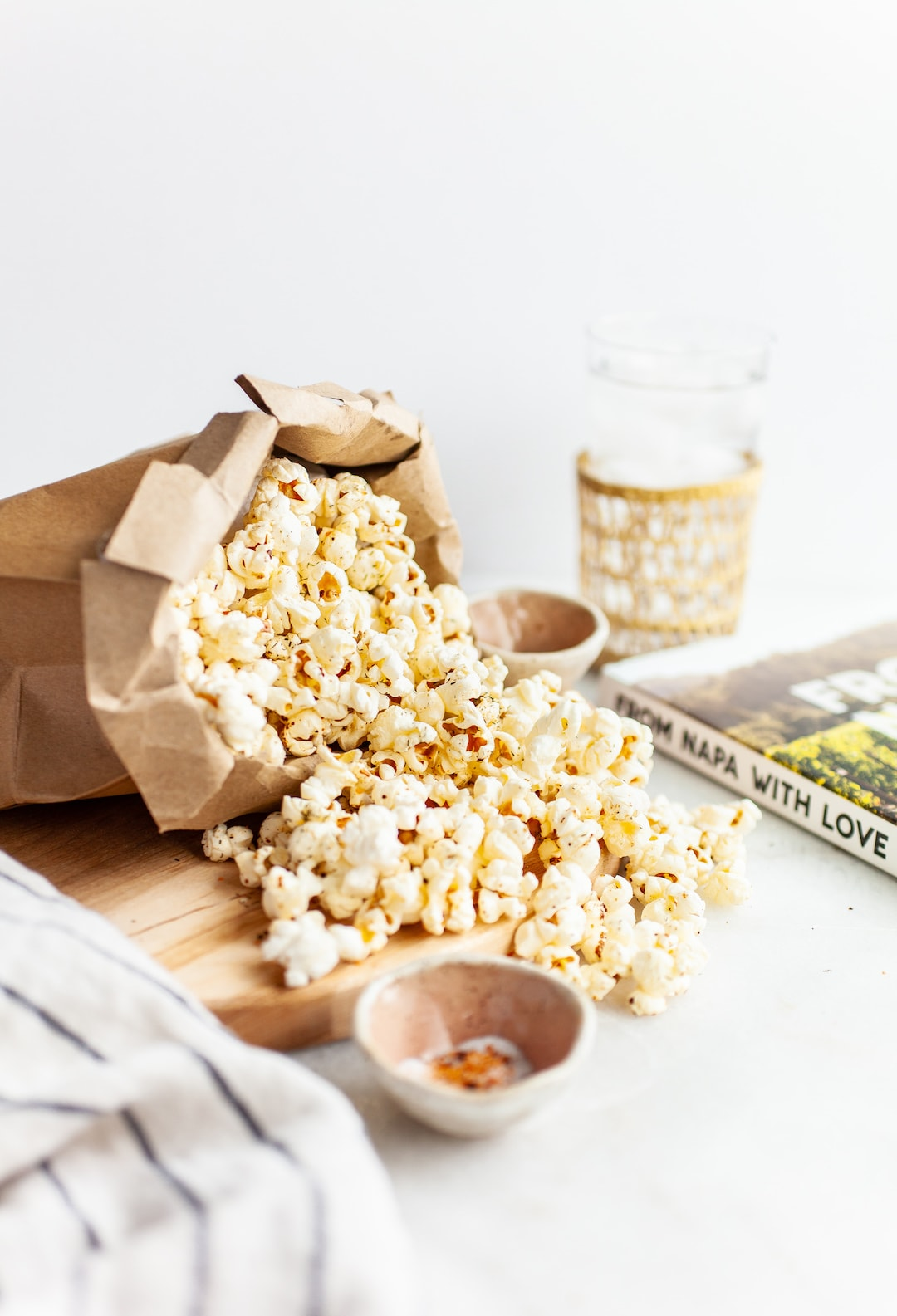 side view of a brown bag of popcorn spilling out onto a wood board
