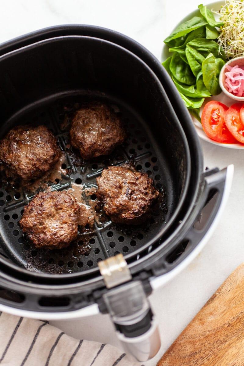 Cooked burger patties in an air fryer basket