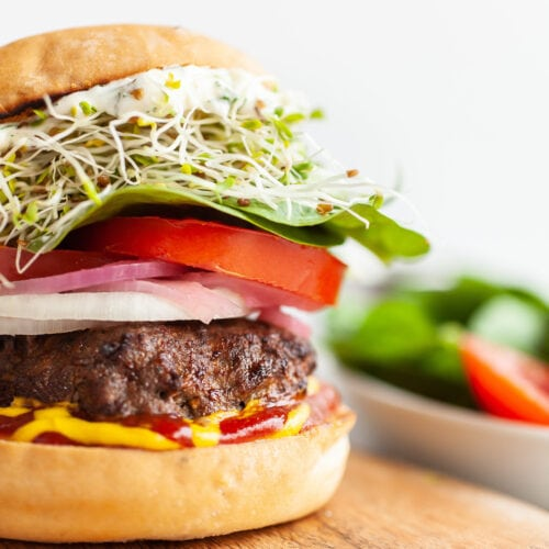 Close up of Air fryer burger with sprouts, lettuce, tomatoes, ketchup and mustard