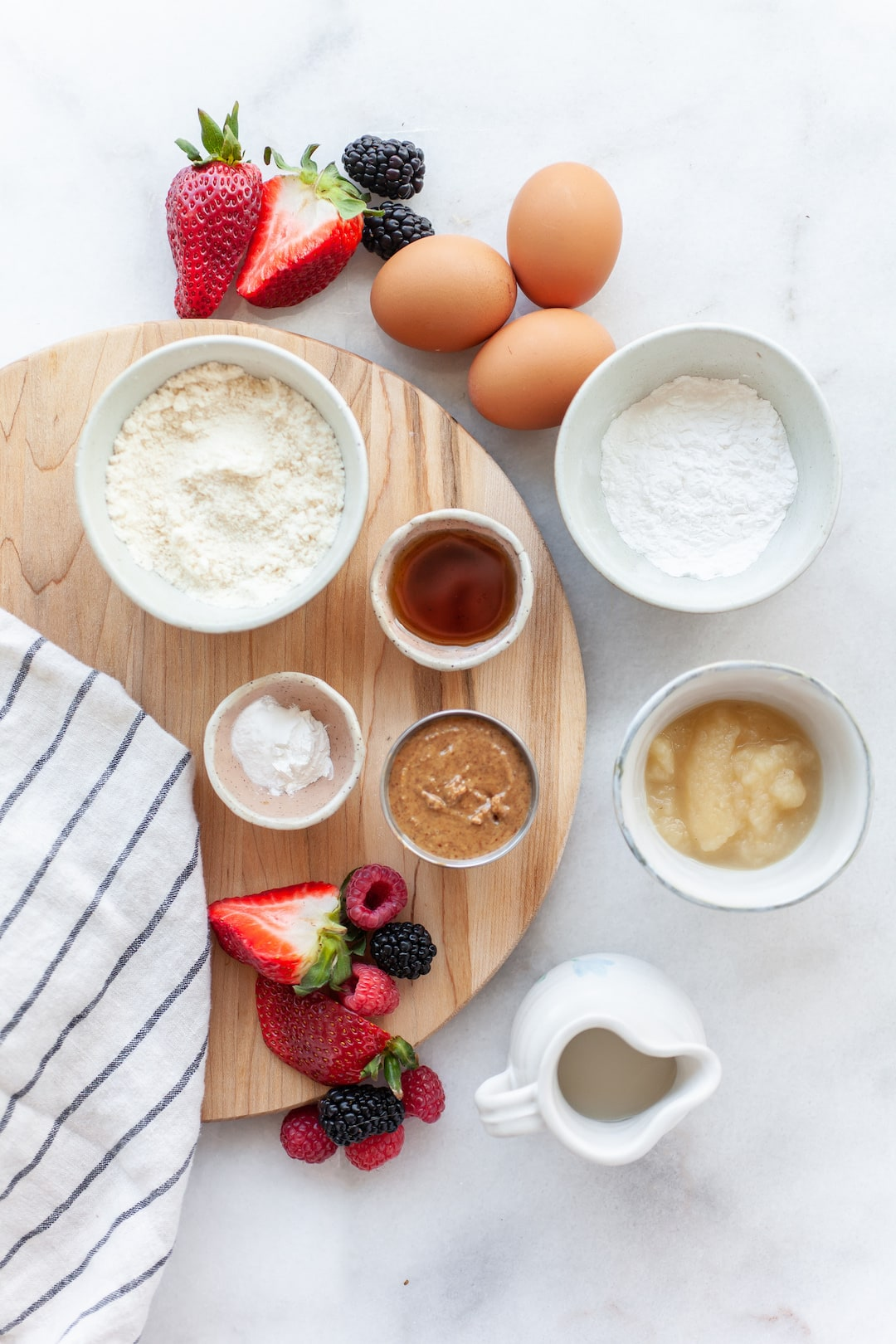 Large white marble board with bowls containing ingredients for Easy Coconut Flour Waffles