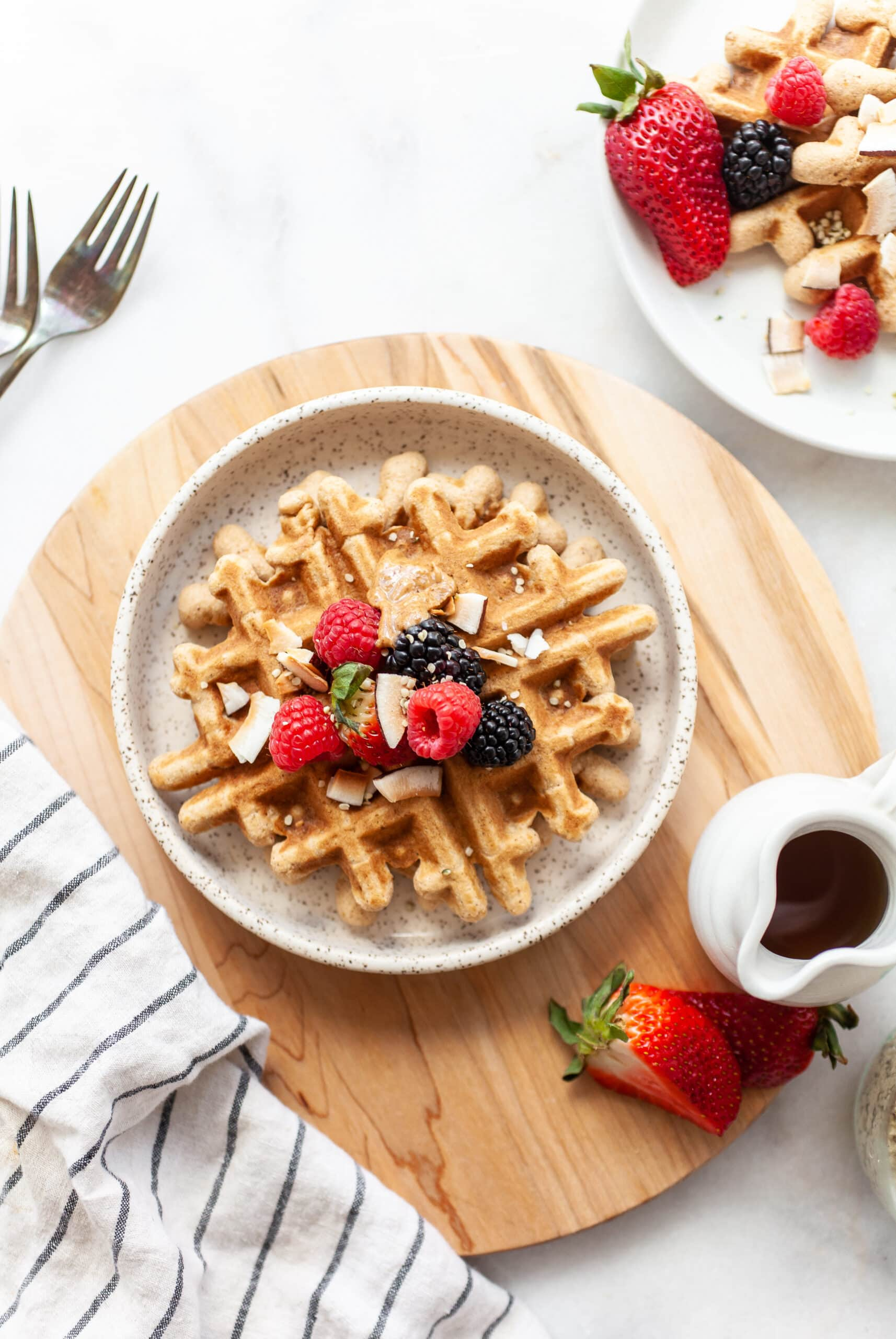 plate with Easy Coconut Flour Waffles on a wooden round board with maple syrup on the side