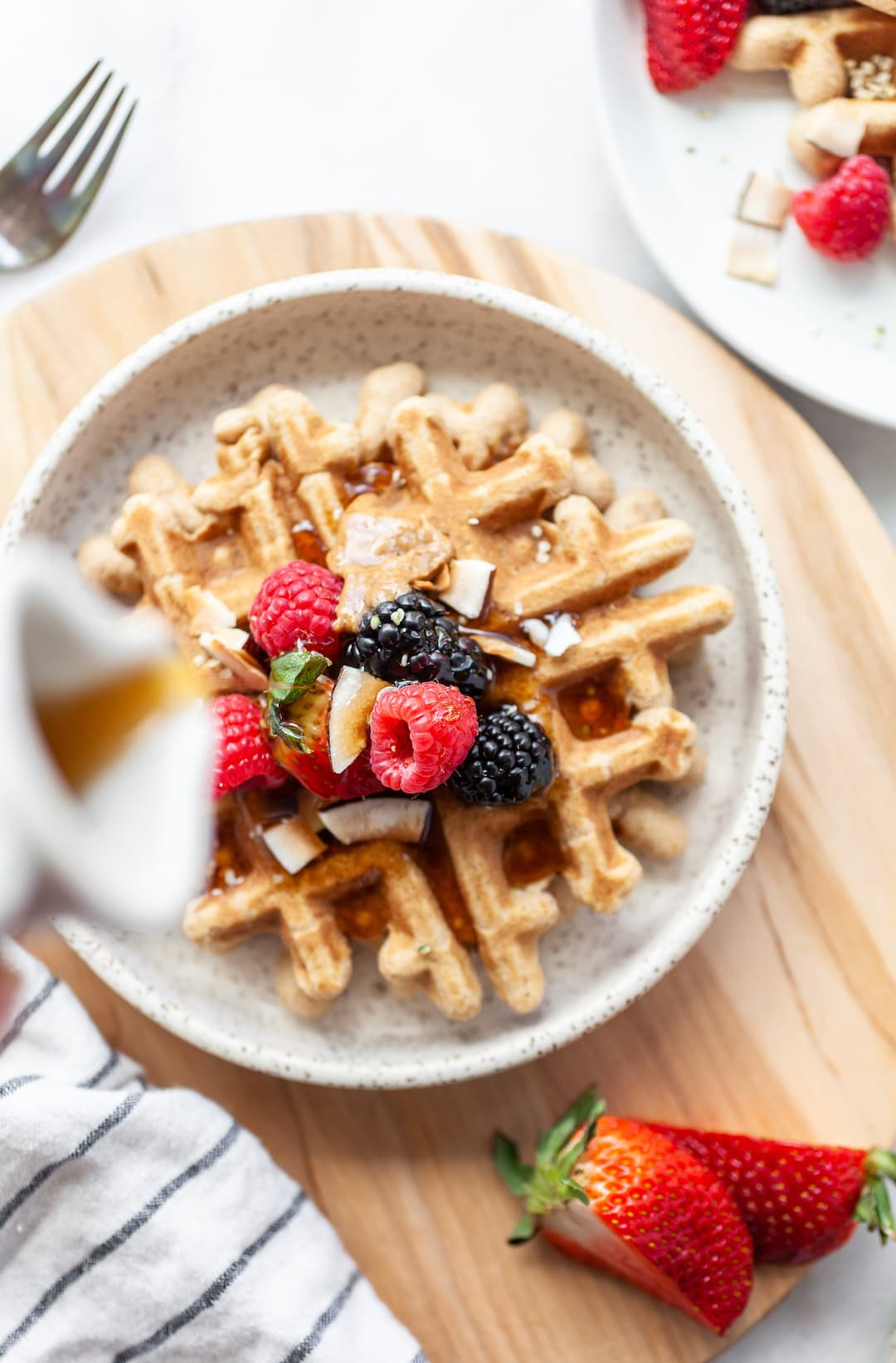 Easy Coconut Flour Waffles on a plate topped with fresh berries and syrup being poured on top