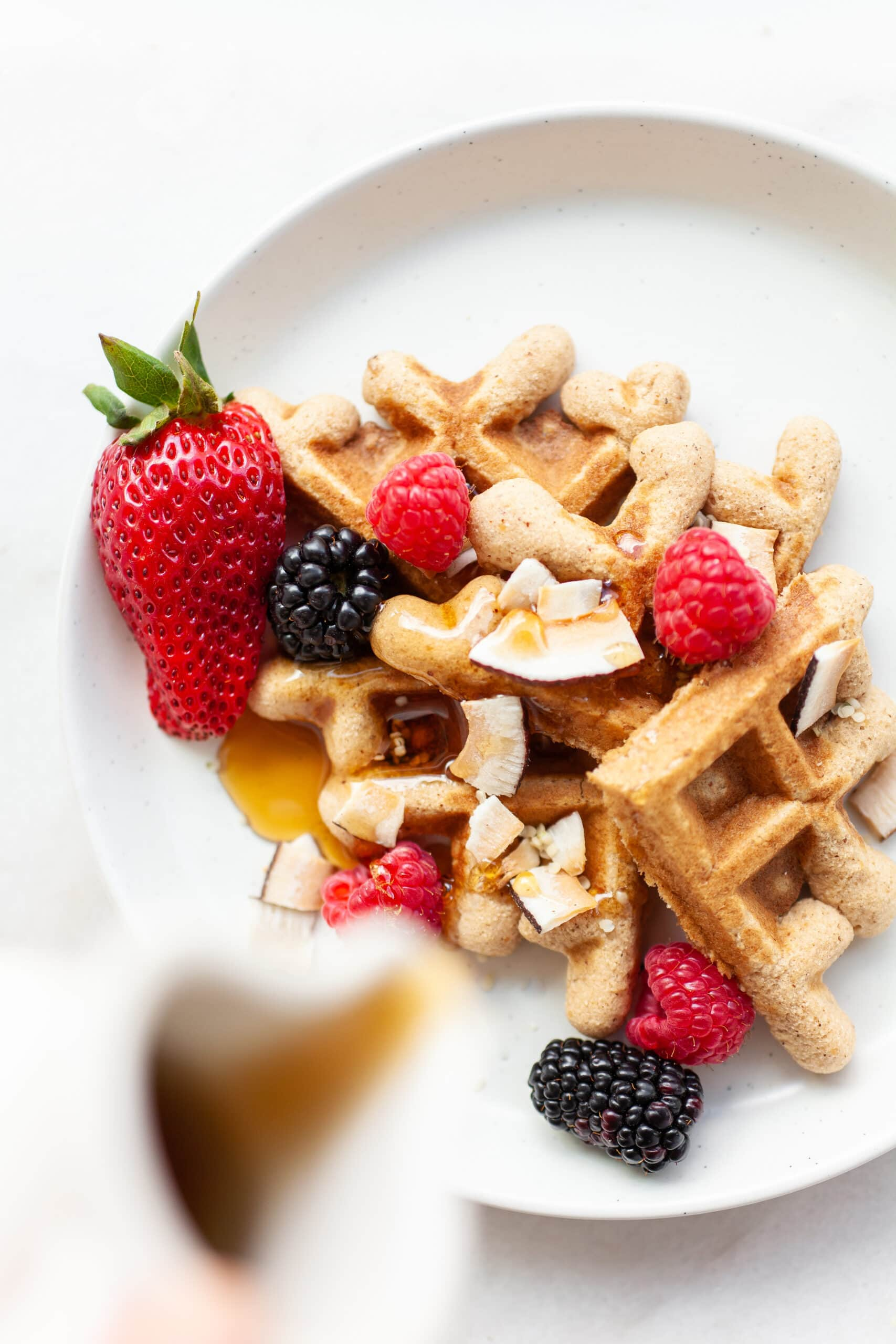 white plate with pieces of Easy Coconut Flour Waffles topped with berries and maple syrup