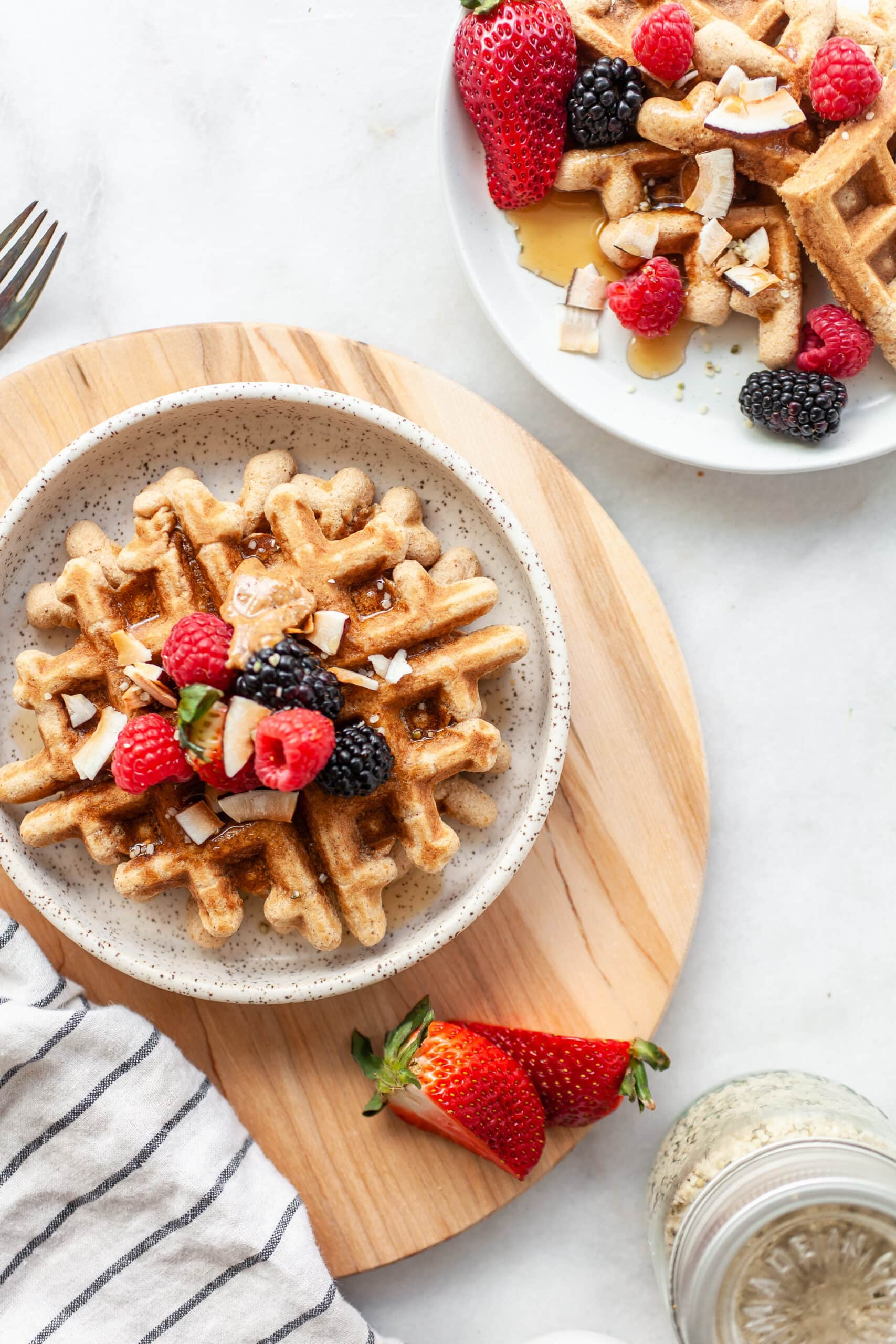 two plate with Easy Coconut Flour Waffles on a wooden round board with maple syrup on the side
