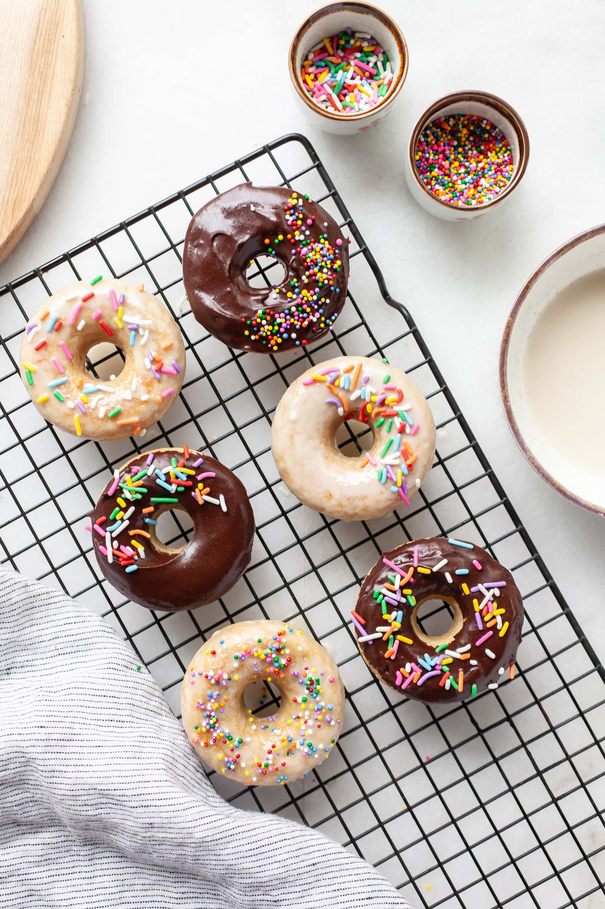 overhead view of six vanilla protein donuts with chocolate and vanilla glaze and rainbow sprinkles