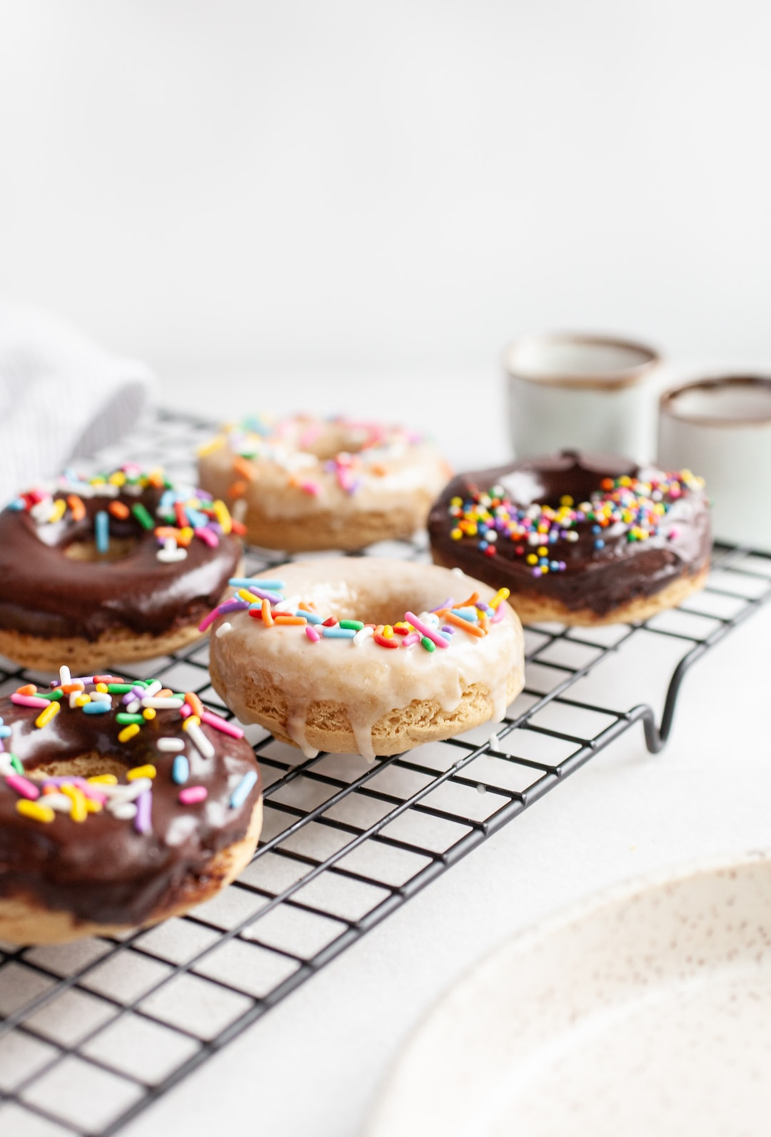 Side view of Simple Vanilla Protein Donuts on a cooling rack with chocolate and vanilla glaze and rainbow sprinkles