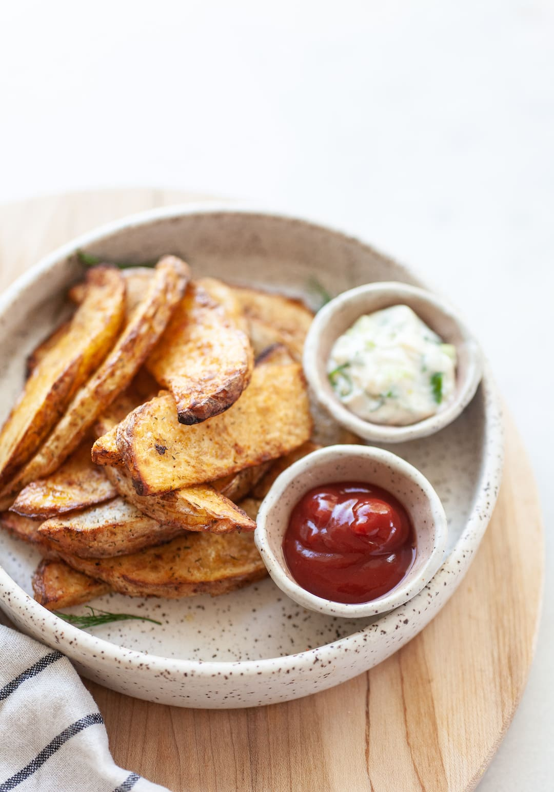 Plate of air fried potato wedges with two ramekins of ketchup and aioli dip
