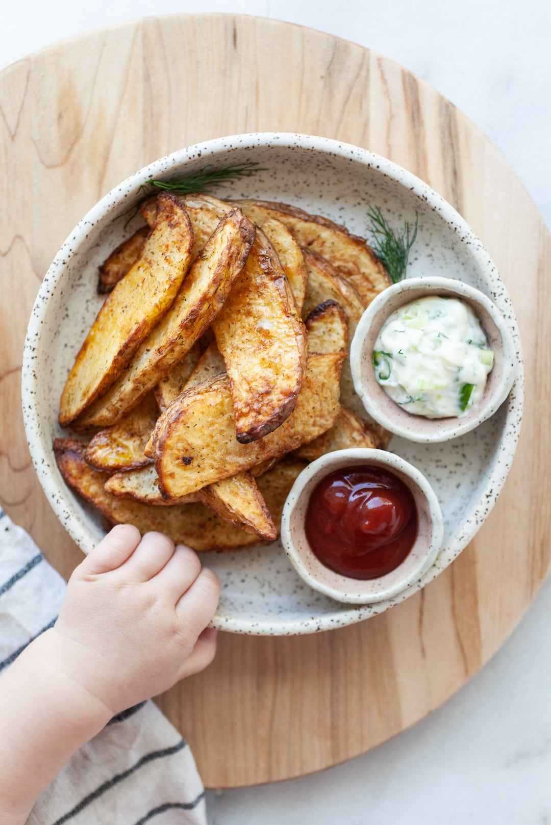 Air Fried Potato Wedges on a plate with a small Childs hand reaching for the plate