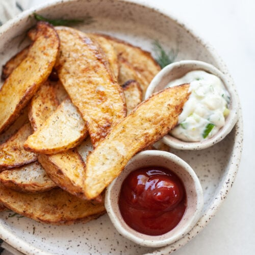 Air Fried Potato Wedges on a plate with one wedge dipped into a small bowl of aioli