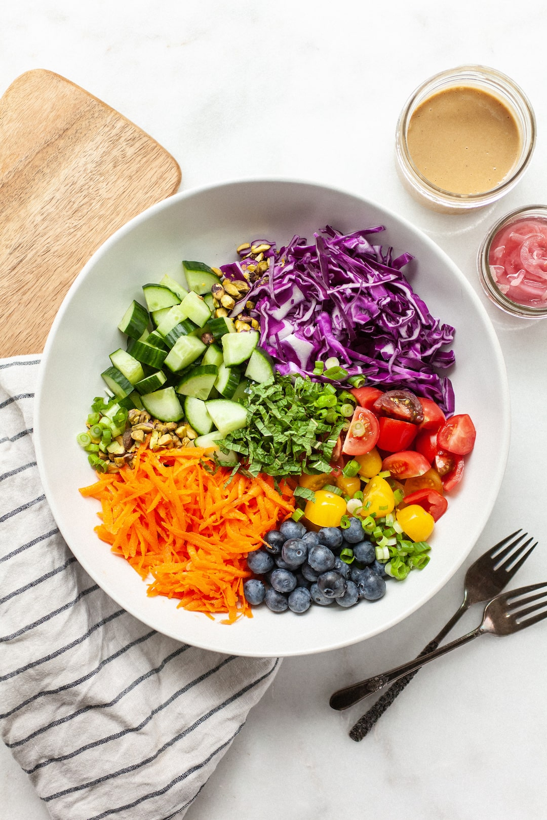 bowl of colourful vegetables including cabbage, cucumber, carrots, and tomatoes