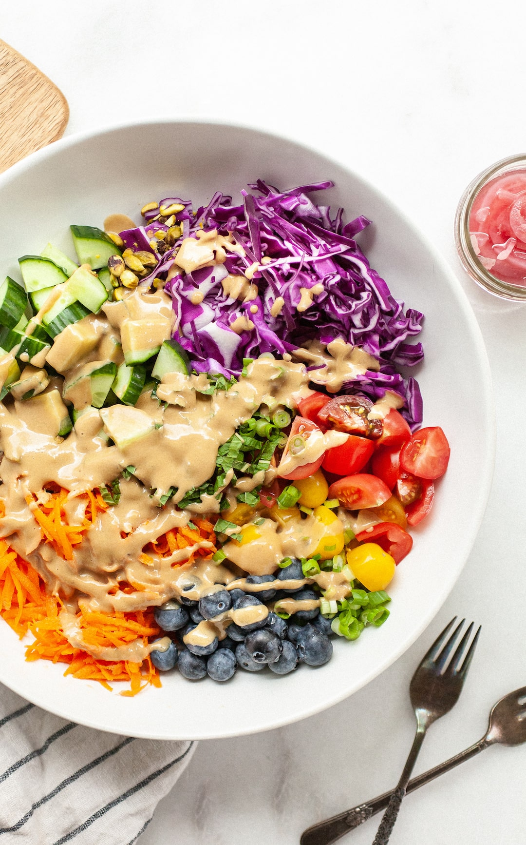 rainbow salad in a large white bowl drizzled with tahini balsamic dressing