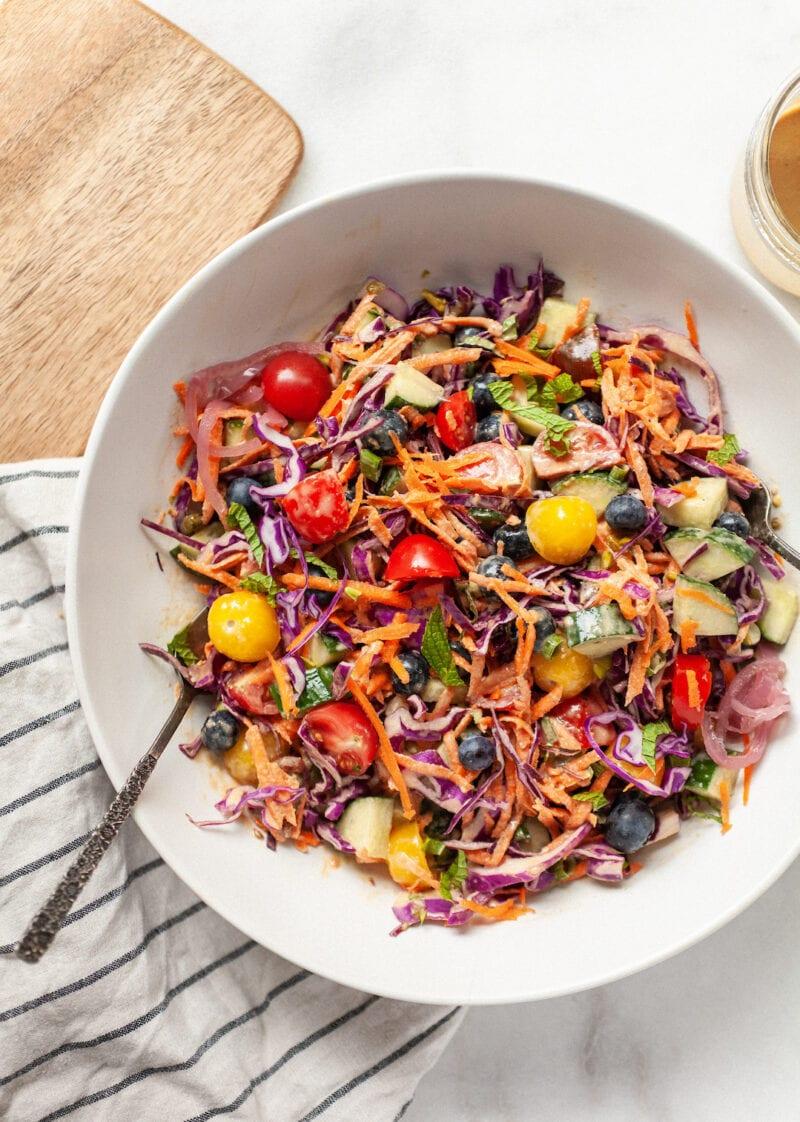 bowl of rainbow salad tossed with tahini dressing