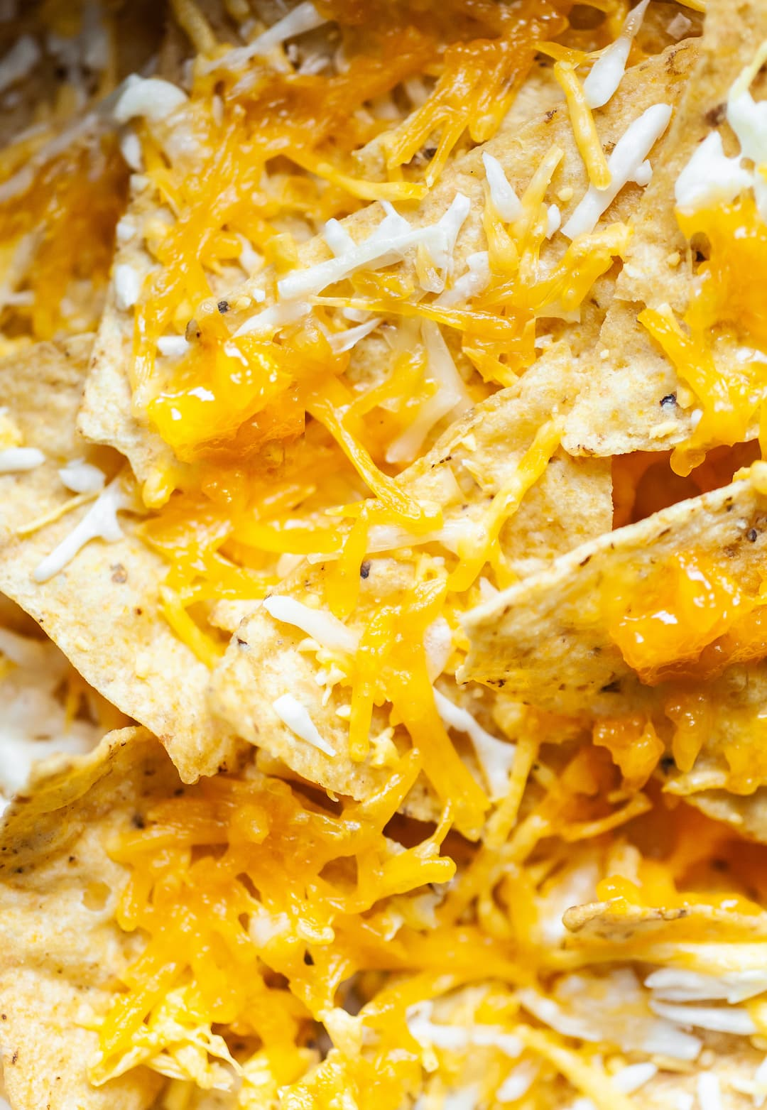 Close up of air fryer nachos - tortilla chips with melted cheese