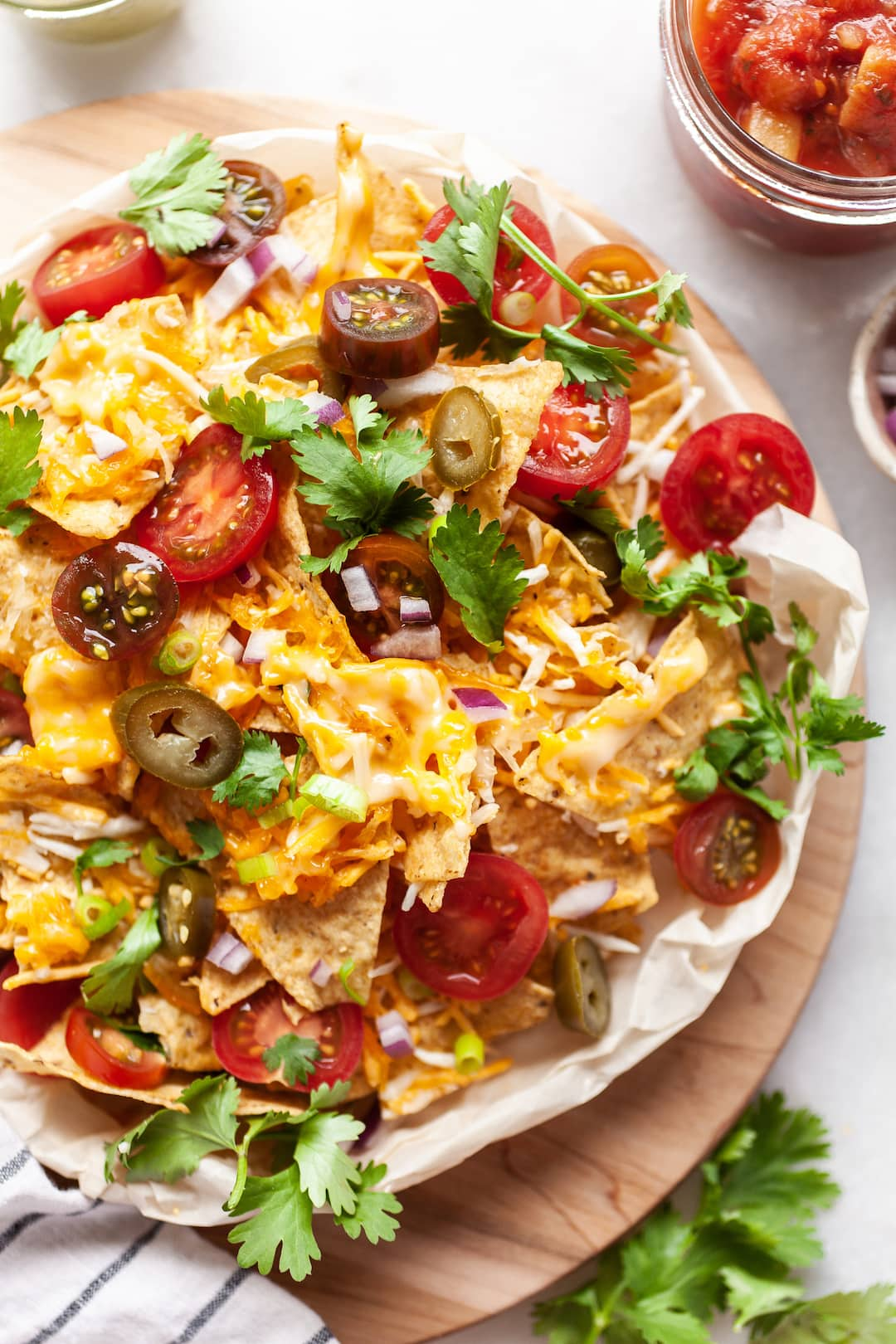 Close up of Air Fryer Nachos on a plate covered with tomatoes, cilantro, onion, jalapeños, cheese, and guacamole