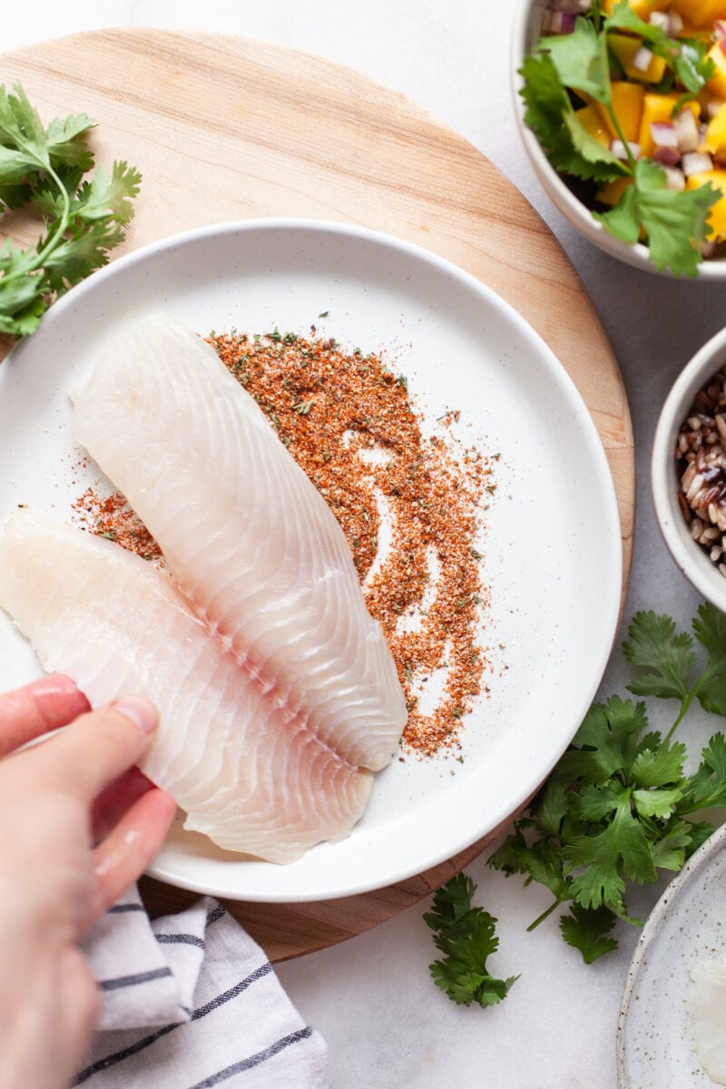 tilapia filets being dipped in a seasoning mixture on a plate