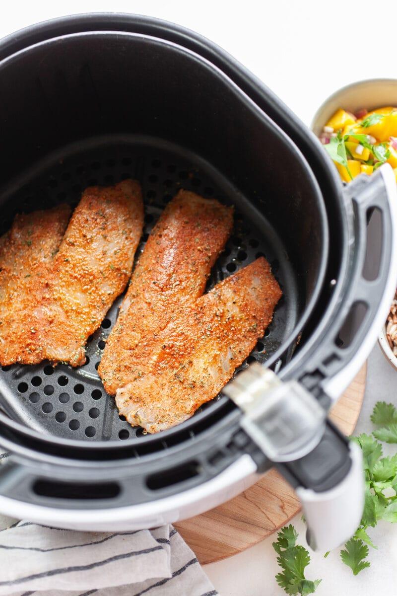uncooked Air Fryer Tilapia in the air fryer basket