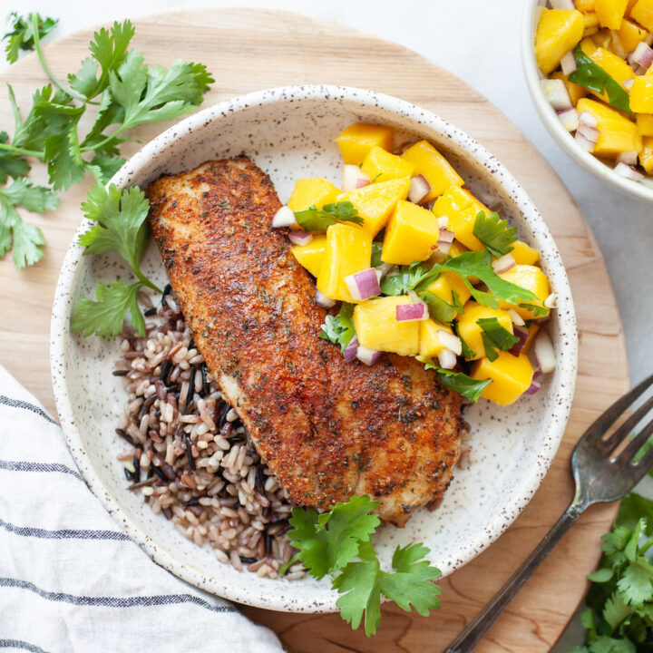Plate of Air Fryer Tilapia on a bed of wild rice with mango salsa and cilantro on the side