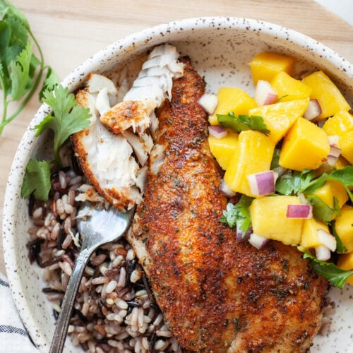 Plate of Air Fryer Tilapia on a bed of wild rice with mango salsa