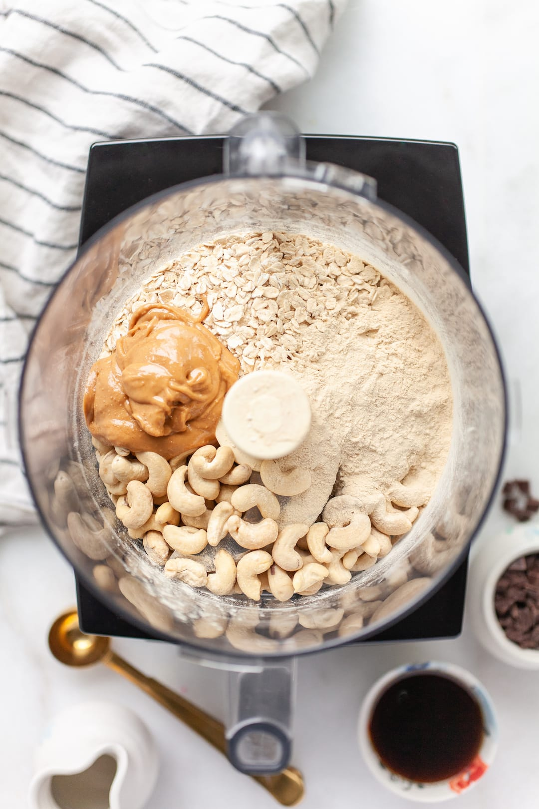 ingredients for protein cookie dough in a food processor - cashews, peanut butter, rolled oats, protein powder