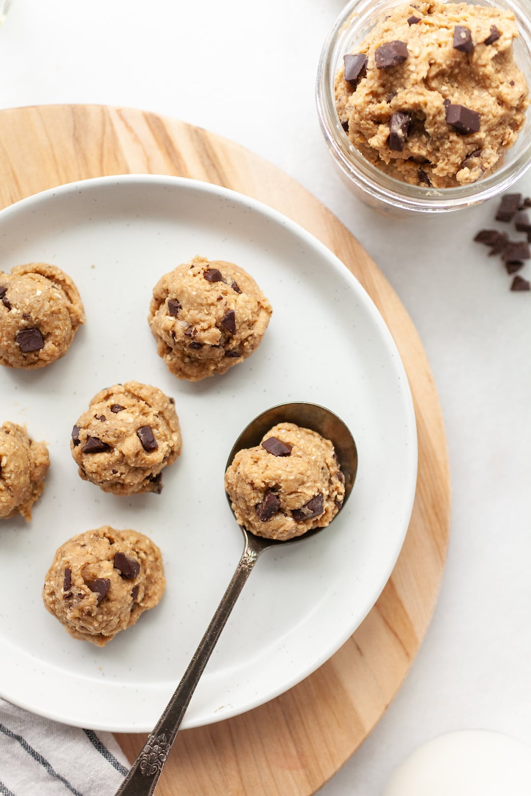 protein cookie dough balls with dark chocolate chunks arranged on a white plate