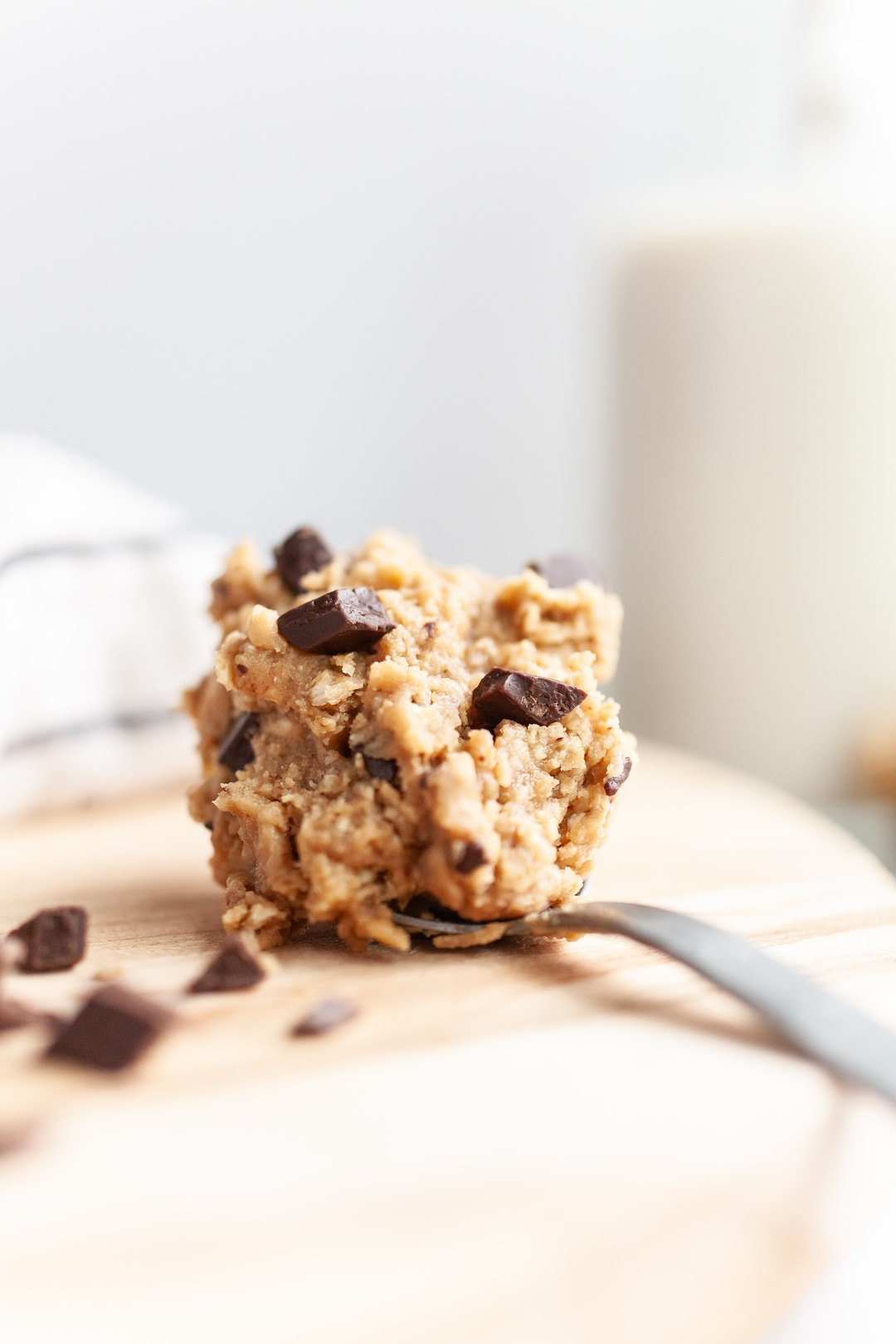 spoon of protein cookie dough with dark chocolate chunks on a wood board