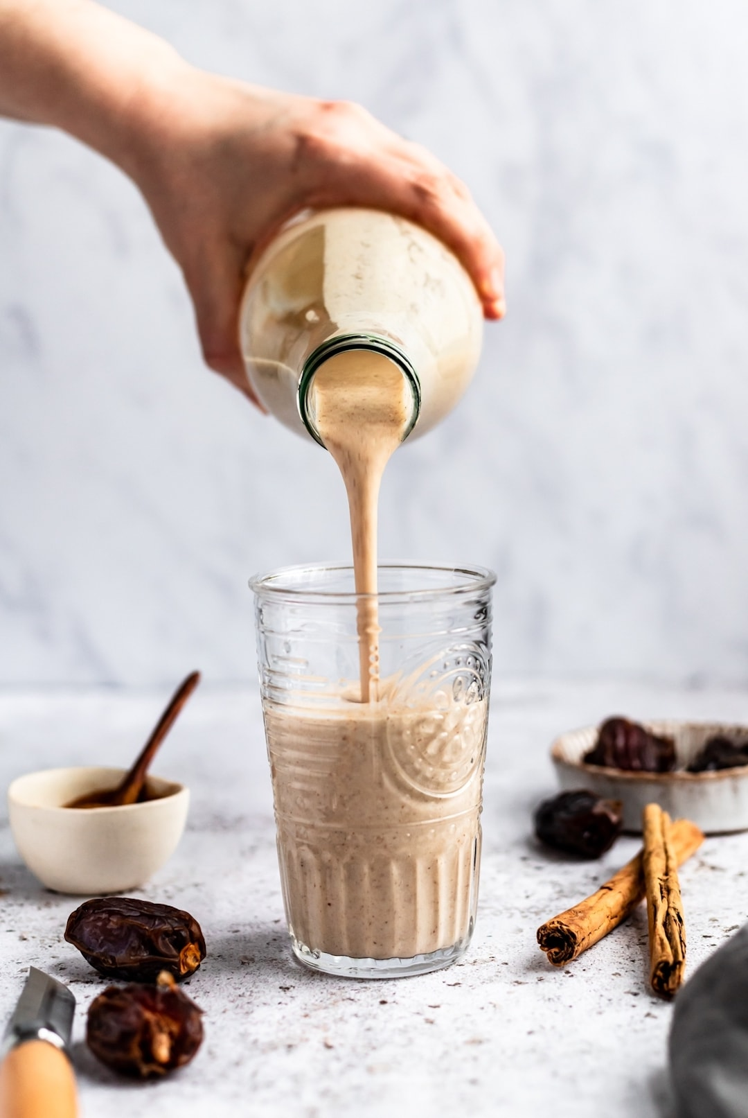 Pouring snickerdoodle smoothie into a glass with dates and cinnamon sticks on the side