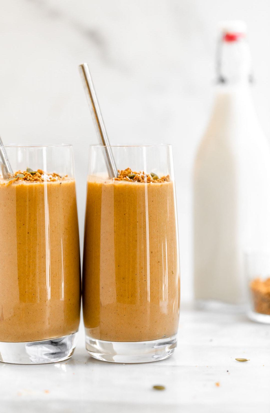 two glasses of sweet potato smoothie with a jar of milk in the background