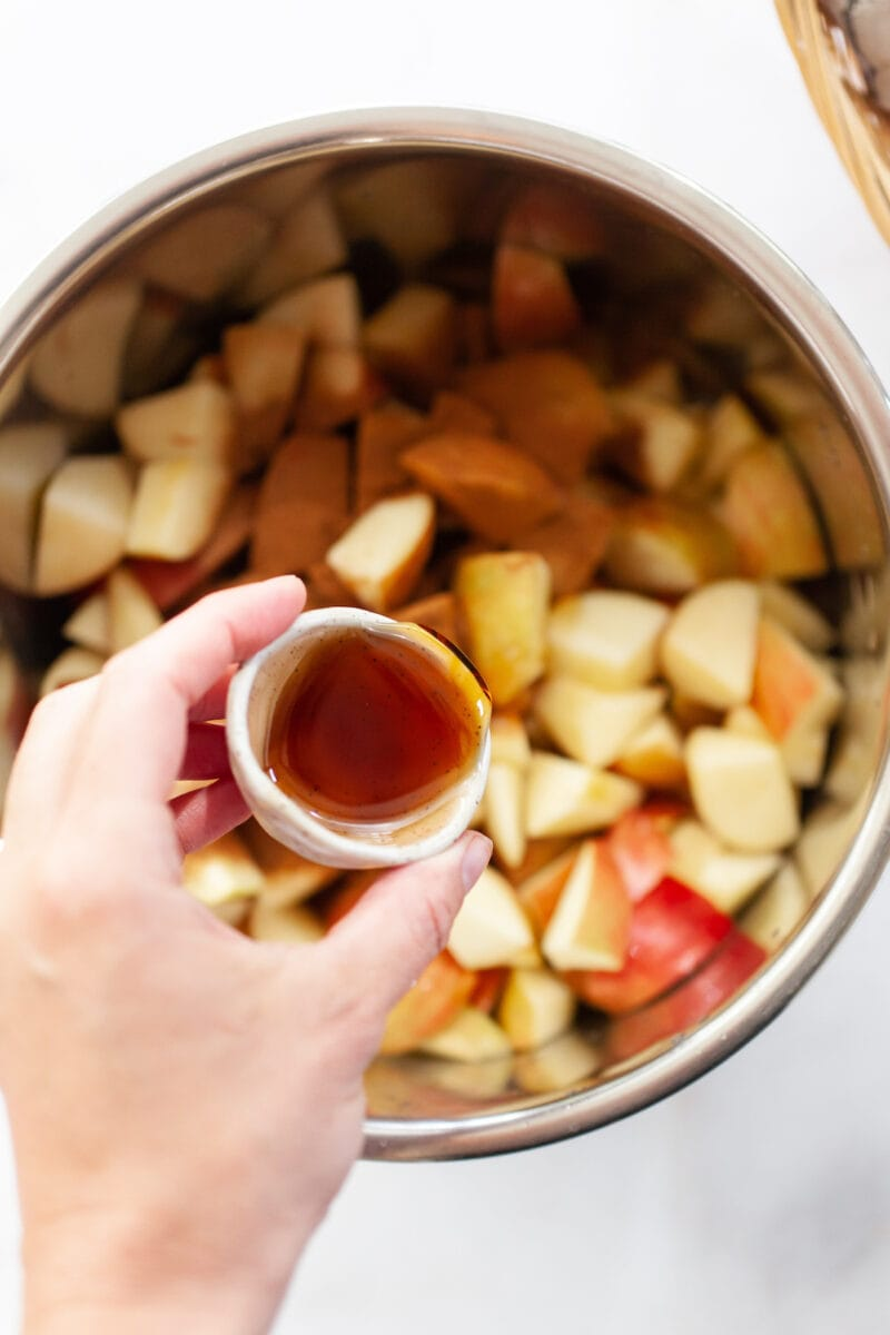pouring maple syrup onto diced apples covered in cinnamon in an instant pot