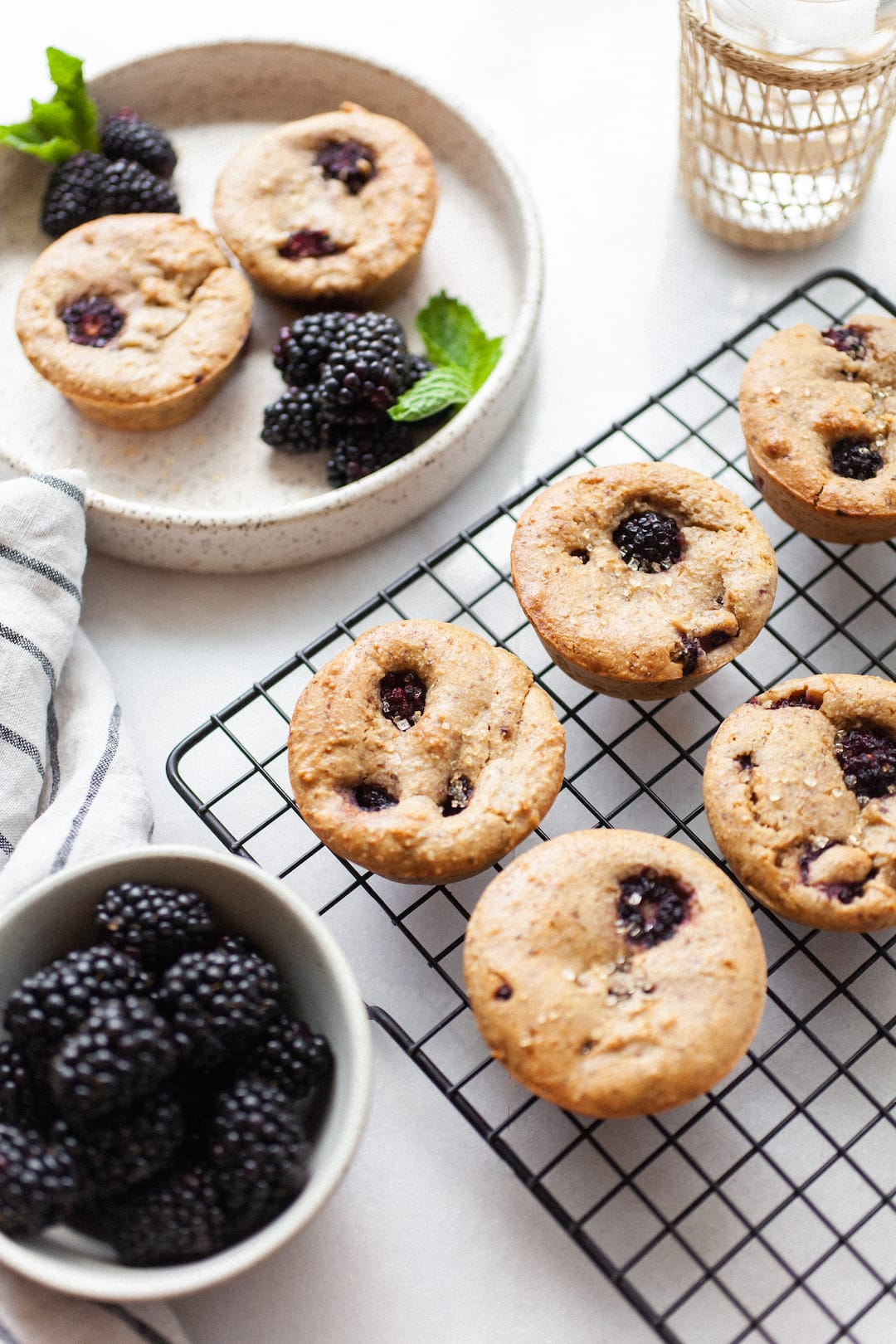 Vegan Blackberry Muffins on a cooling rack beside a bowl of blackberries