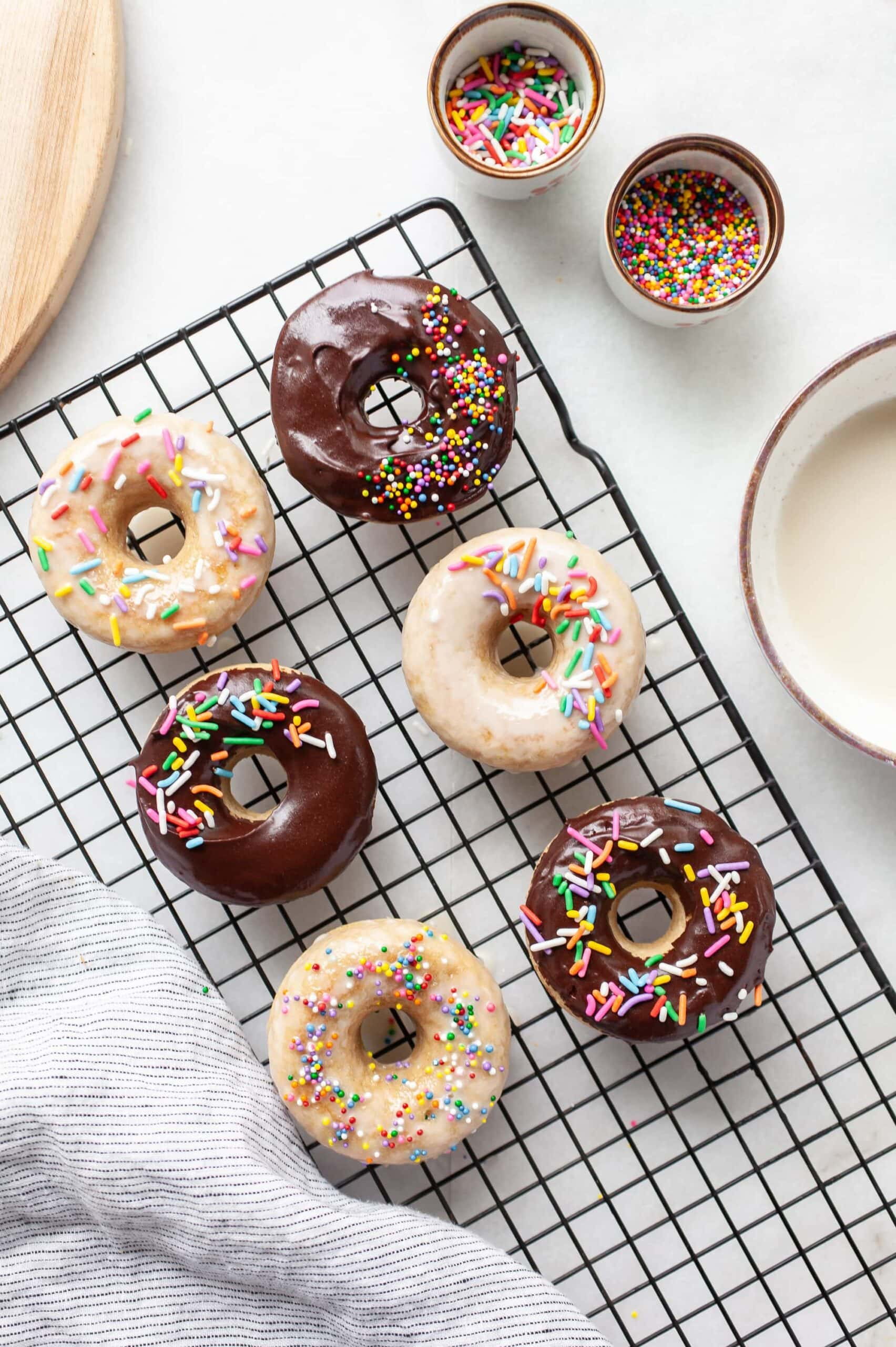cooling rack topped with protein donuts covered in chocolate and vanilla glaze and rainbow sprinkles