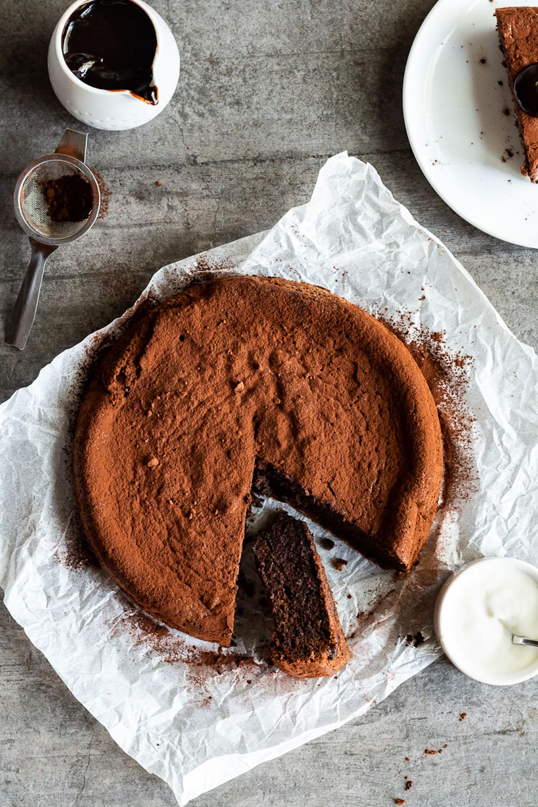 flourless chocolate cake on a parchment paper and wood board background