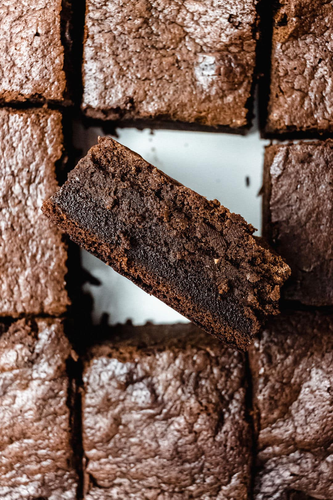 tray of gluten free brownies with one brownie in the middle turned on its side