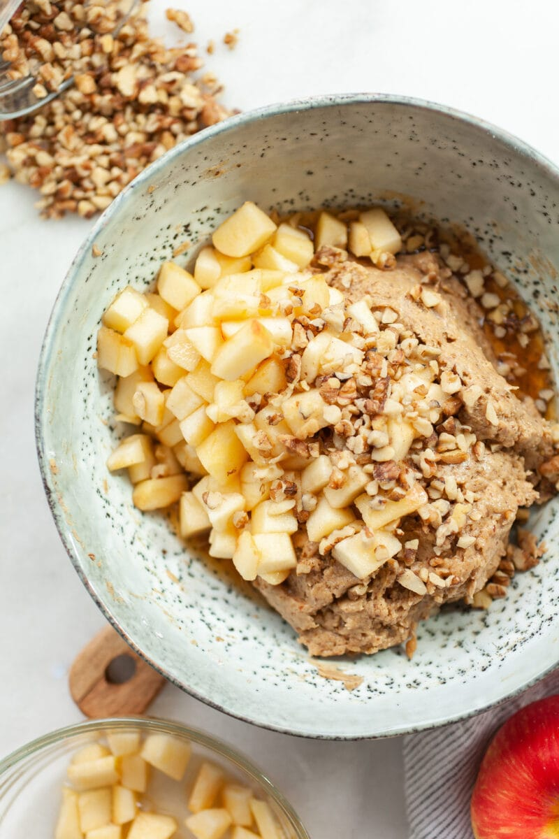 vegan apple cake batter in a green bowl with fresh apple cubes and walnuts