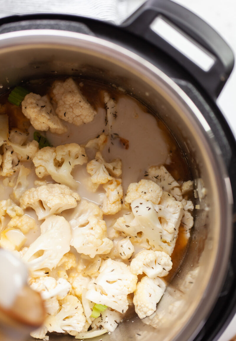 image of cauliflower in an instant pot with broth and milk