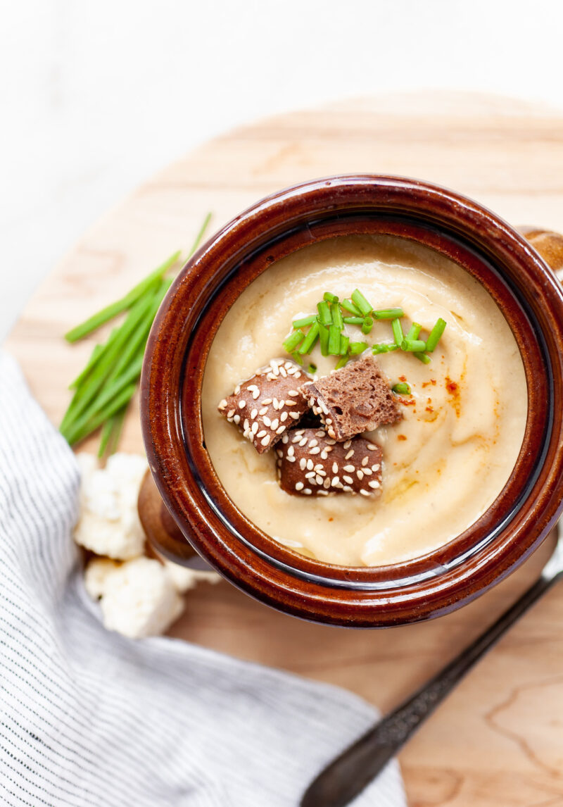 image of instant pot cauliflower soup in a rustic bowl with croutons and chives on a wood board with chives on the side