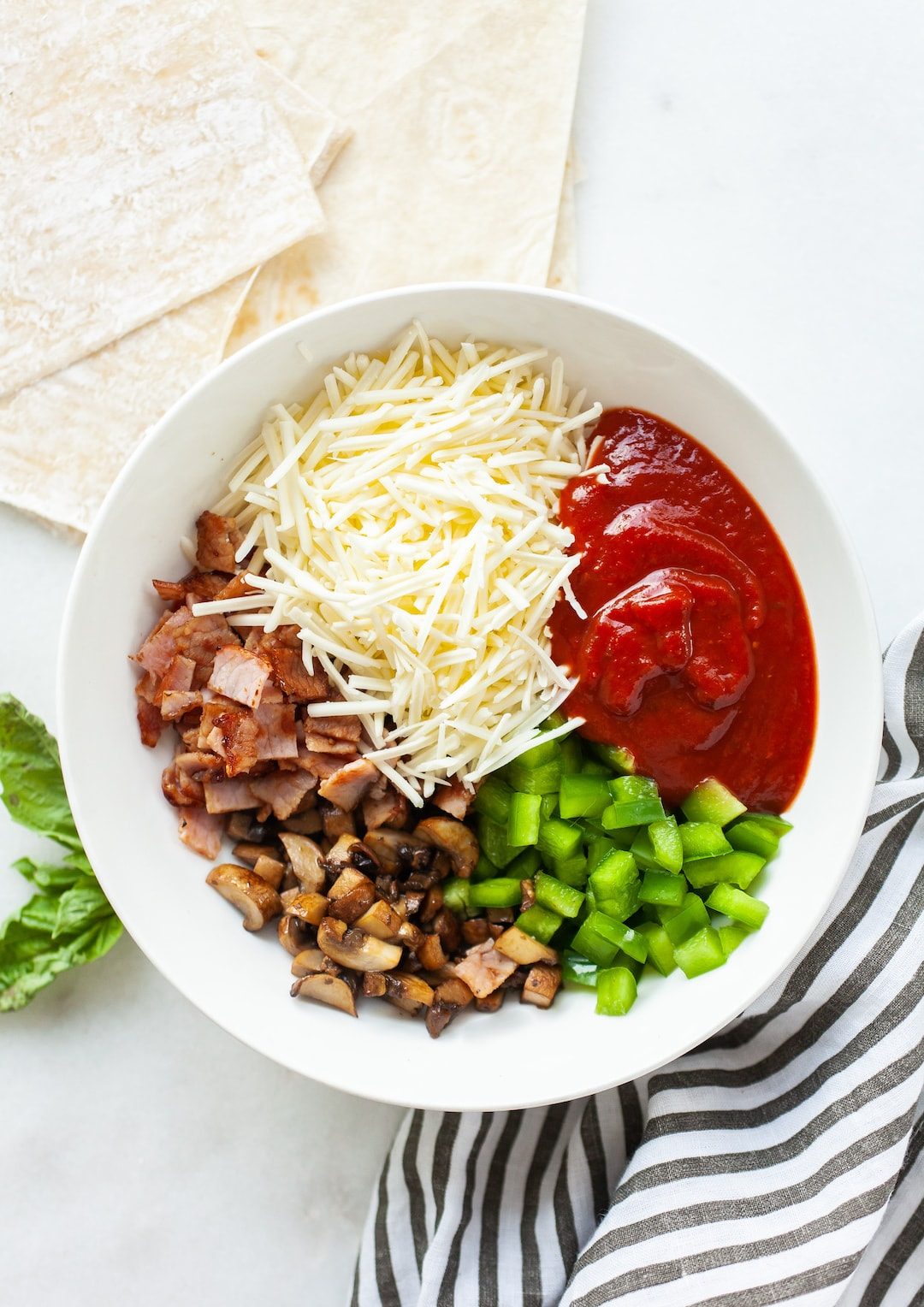Image of a white bowl with air fryer pizza roll ingredients
