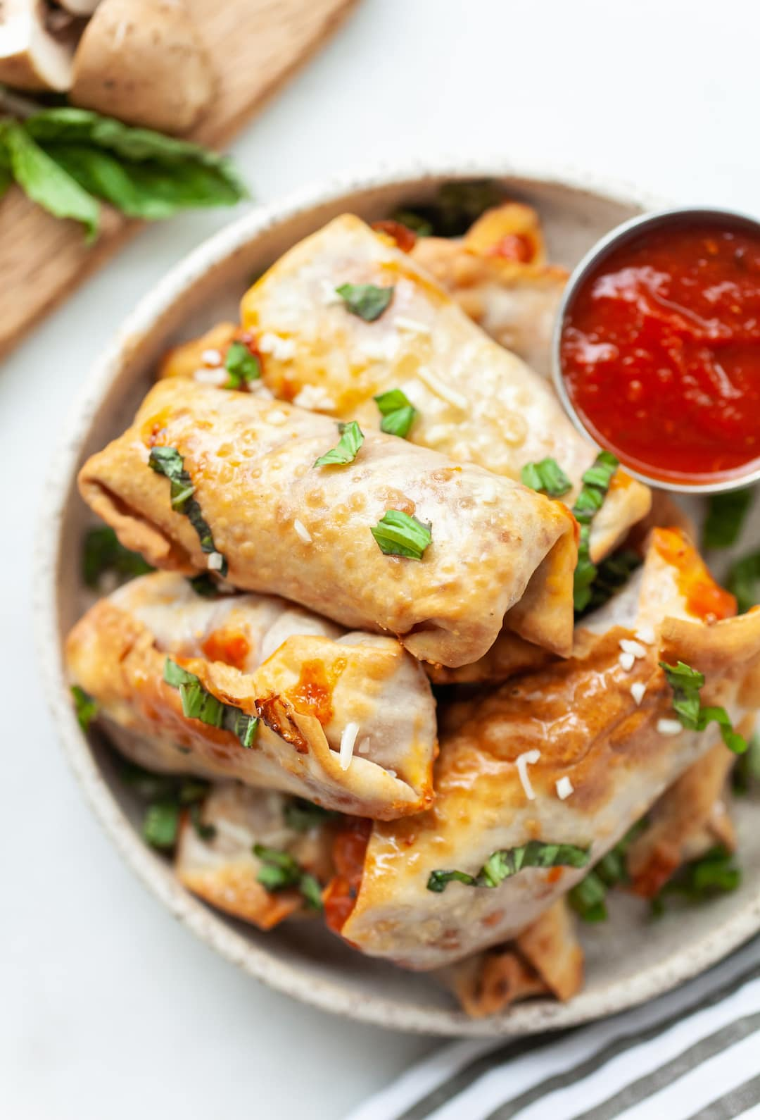 image of air fryer pizza rolls on a plate with pizza sauce on the side