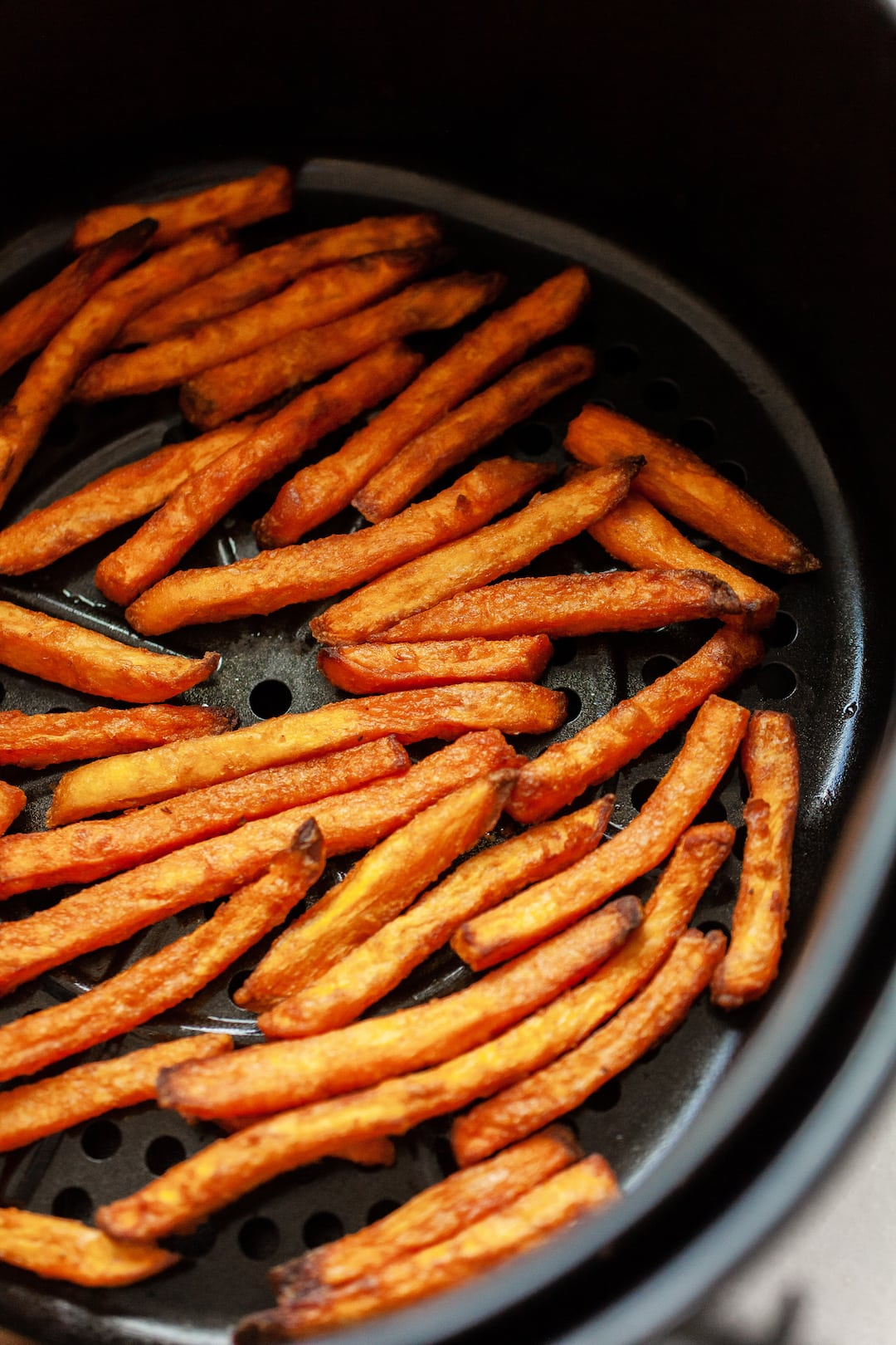 cooked frozen sweet potato fries in an air fryer basket