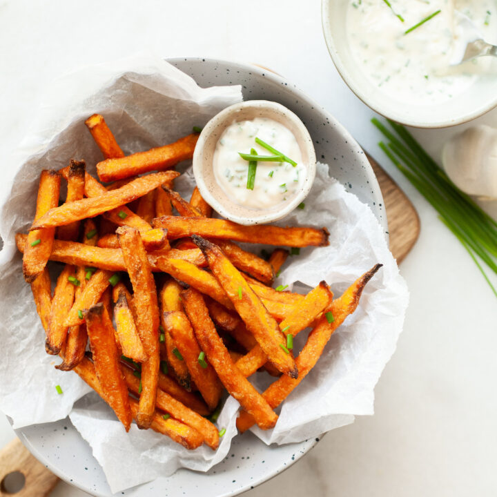 cooked air fryer sweet potato fries in a bowl with chive dipping sauce on the side