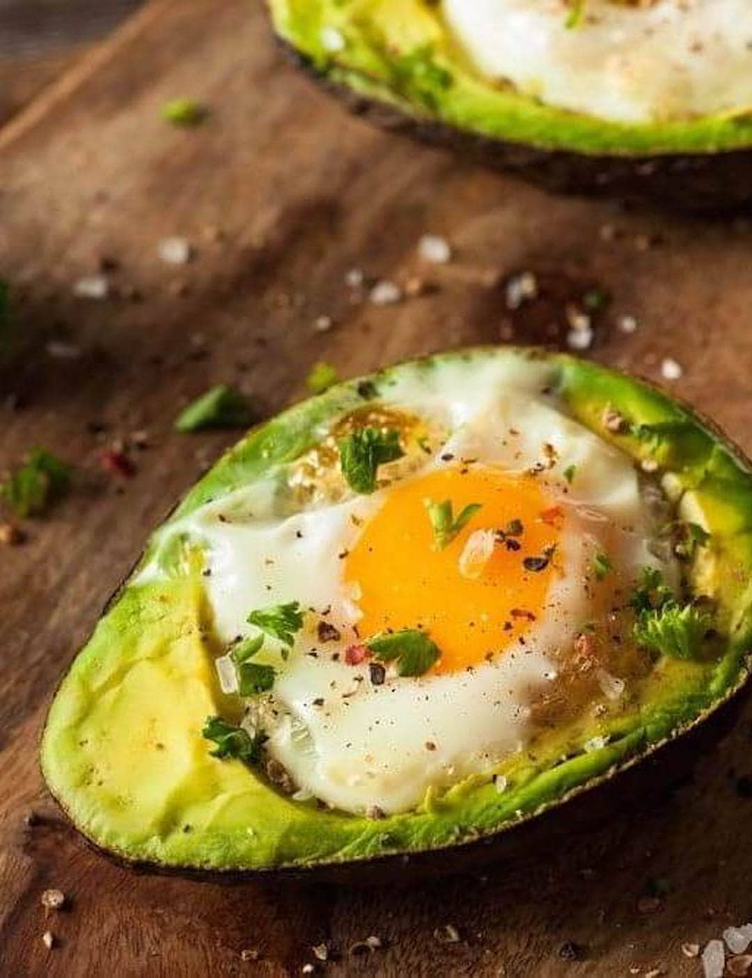 image of an air fryer avocado with egg on a wood platter