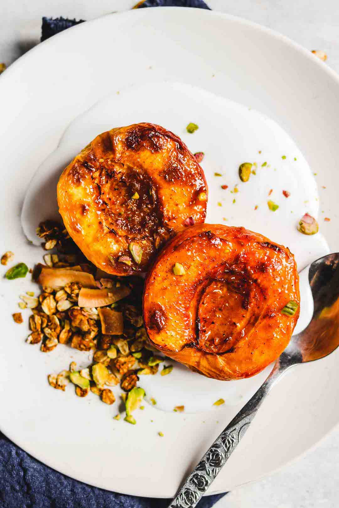 image of two air fried stone fruits on a plate with pistachios