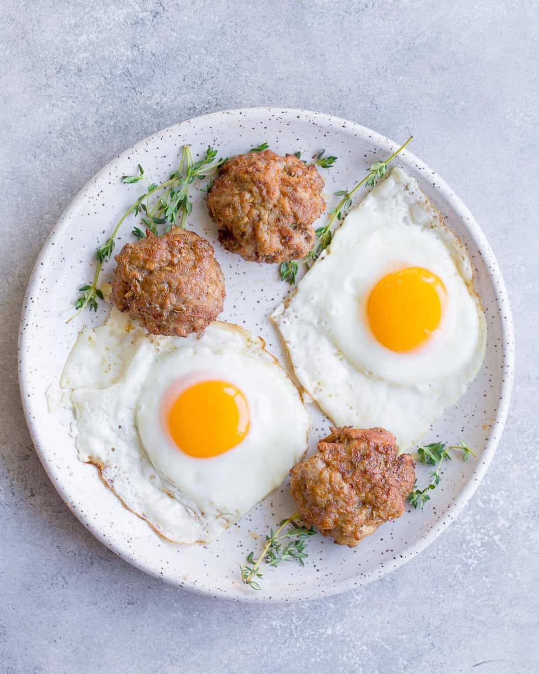 image of a white plate with two fried egg and air fryer breakfast sausages